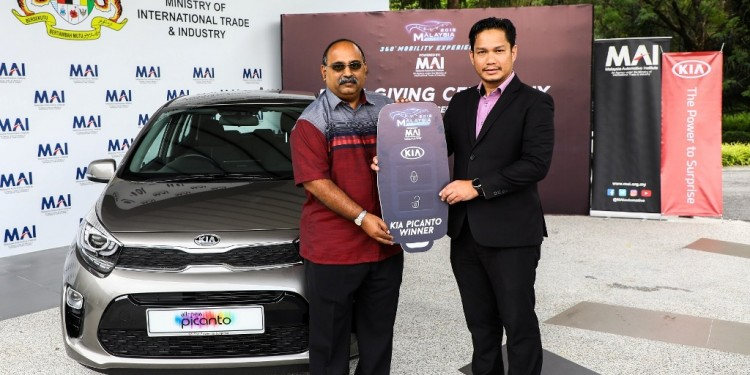 Mr Velu Kumar (left) receiving his Kia Picanto from MAI CFO Mohd Sazali bin Mohamed Amin
